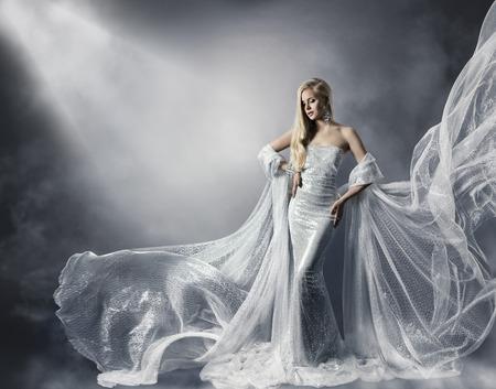 光沢のファッションのドレス、飛行服の女性、星光の光沢のある布でひらひらと流れる下の女の子の若い女性