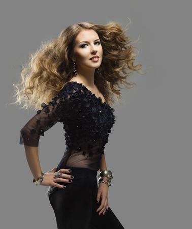 Frau Frisur Porträt, Fliegen langes lockiges Haar, Girl Fashion Schönheit, Windy Haare auf grauem Hintergrund
