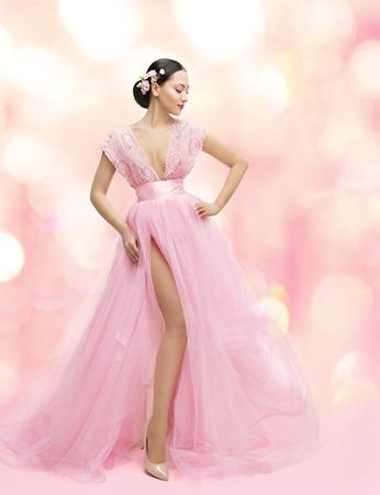 donne eleganti: Donna di bellezza del ritratto in abito rosa con fiore di Sakura, Asian Fashion abito della ragazza, bel modello su sfondo Unfocused