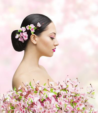 Woman Beauty Portrait in Sakura Flower, Asian Girl Bun Hairstyle, Beautiful Model Over Pink Background photo