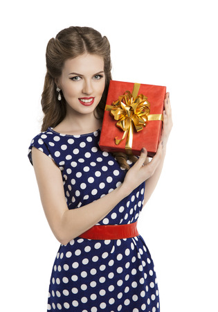 Woman Giving Gift Box, Girl in Retro Polka Dot Dress Advertising Red Present, Pin Up Beauty Hair Style, Isolated Over White Background photo