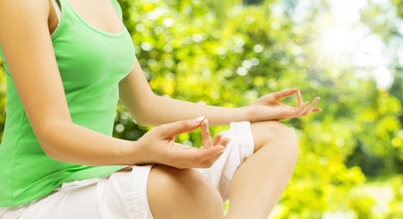 meditation woman: Yoga Meditation, Sitting Outdoors in Lotus Pose, Woman Meditating Hand over Green Unfocused Park Stock Photo