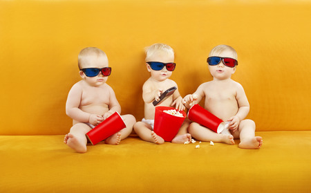Baby 3D Glasses Watching Film On TV, Children Eating Popcorn And Watch Cinema Movie In Home Theater, Kids In Diapers With Remote Control photo