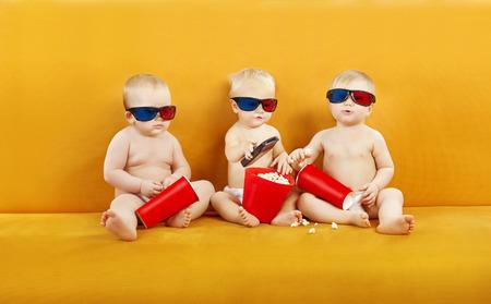 Dzieci: Dziecko Okulary 3D Oglądanie programu w telewizji, dzieci jeść popcorn i oglądać film w Cinema kina domowego, dla dzieci w pieluchach z pilotem Zdjęcie Seryjne