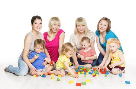 niñez: Grupo de niños con madres que juegan bloques de juguete. Little Kids Desarrollo Temprano. Niños Juegos Activos, aislado más de fondo blanco Foto de archivo