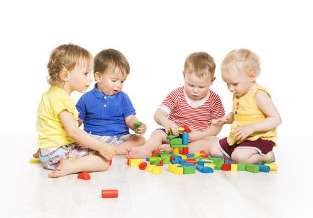 niños jugando en la escuela: Grupo de niños que juegan bloques de juguete. Little Kids Desarrollo Temprano. Bebé actividad un año viejos juegos, aislado más de fondo blanco