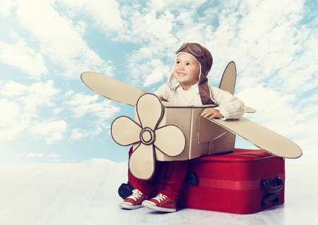 travellers: Little Child Playing Airplane Pilot, Kid Traveler Flying in Aviator Helmet on Travel Suitcase, Vacation Trip Concept over Blue Sky Clouds