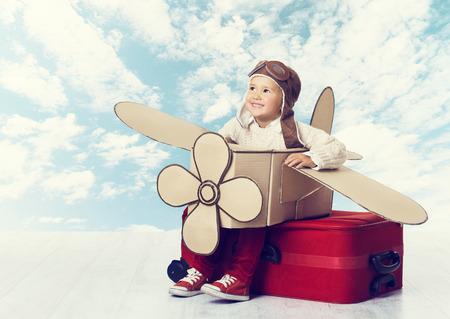 Pequeño niño que juega piloto de avión, Kid Flying Traveler en Aviator Casco en la maleta del recorrido, el concepto de vacaciones de viaje sobre el cielo azul Nubes