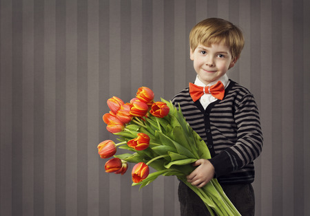 flowers boy: Little Child Boy Giving Flowers Bouquet, Handsome Kid Greeting Red Tulips Bunch, Retro Style Celebration, Looking at Camera