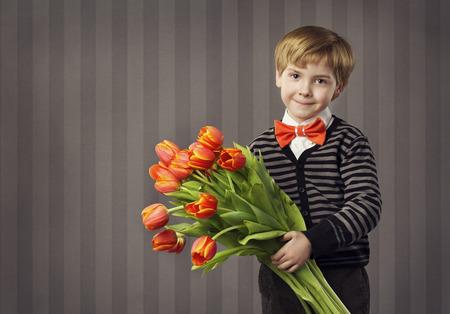 florecitas: Niño Pequeño Niño que da el ramo de las flores, Kid Hermoso Tarjetas rojas de los tulipanes Bunch, Retro Celebración Estilo Mirando a la cámara