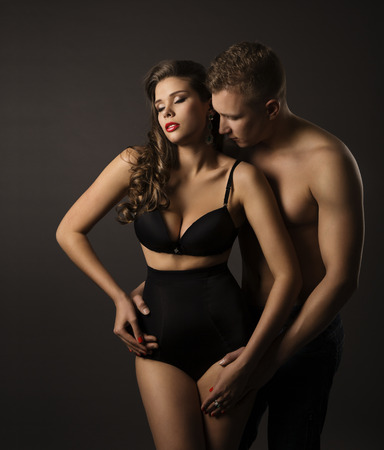 breast beauty: Sexy Couple Woman and Man Portrait, Female in Sensual High Waist Underwear Panties, Kissing Boyfriend over Black Background Stock Photo