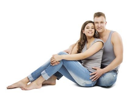 Young Couple Portrait, Happy Girl and Boy Friend in Jeans, Woman and Man Sitting Isolated over White Background photo