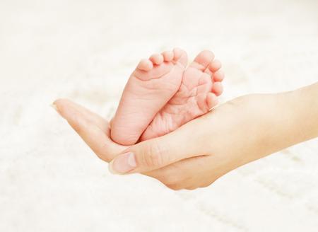 ragazza innamorata: Neonato piedi in mani della madre. New Born Kid piede, Famiglia Concetto Amore