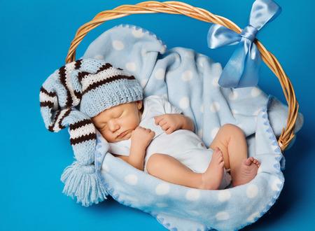 Bebê recém-nascido dentro da cesta, New Born Kid sonho no chapéu de lã, menino Criança dormindo sobre o fundo azul Foto de archivo