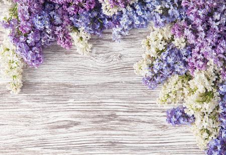 flores moradas: Lila florece el ramo en tabl�n de madera de fondo, primavera p�rpura Blooming Bunch, Rama sobre textura de madera Foto de archivo