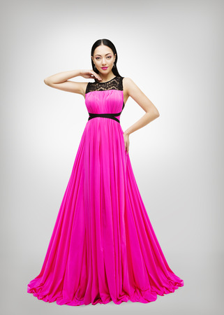 Long Dress, Young Fashion Model in Pink Gown High Waist, Woman in Beauty Clothes Isolated over Gray photo
