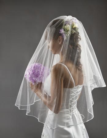 Novia Velo Retrato, novia de la boda del estilo de pelo con las flores del ramo, joven novia antes de la ceremonia de boda