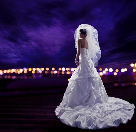 vestido de noche: Novia en vestido de novia con velo, Moda Belleza Retrato nupcial, Long drapeado tela con pliegues, Vista posterior durante la noche Luces de la ciudad Cielo