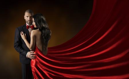 金持ち: カップルの美しさの肖像画、赤いドレスを着て、豊富な女性のガウン、絹の布を振ってスーツ女性の男