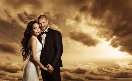 rich couple: Rich Couple Portrait, Elegant Woman Dress and Man Suit with Bow Tie, Fashion Beauty over Evening Sky Stock Photo