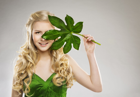Woman Face and Green Leaf, Hair Organic Treatment and Skin Care Concept, Young Girl with Long Blond Hairs over Gray Background photo