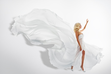 Frau Weiß wellenartig bewegendem Kleid, Zeigen Hand Up, Fliegen Stoff, Seidenstoff Fließen von der Wind Standard-Bild