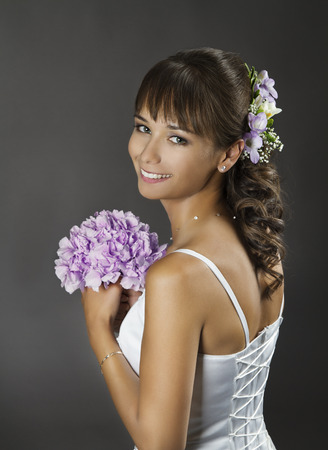 Bride Portrait with Flowers Bouquet, Wedding Hairstyle Makeup over gray background photo