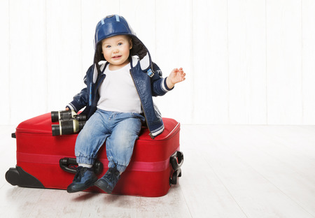 Baby and Suitcase, Kid Sitting on Luggage, Child Boy in Leather Jacket Helmet, Children Vacation Travel Concept Stock Photo