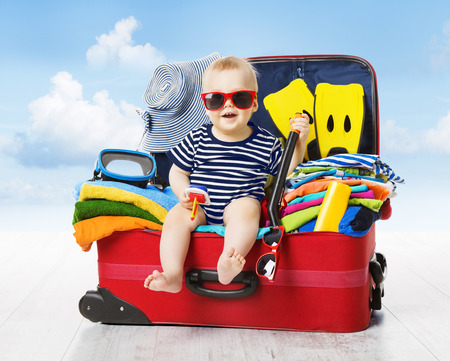 family with one child: Baby in Travel Suitcase. Kid inside Luggage Packed for Vacation Full of Clothes, Child and Family Trip