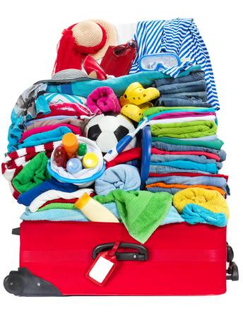 maleta: Maleta del recorrido lleno para vacaciones en el centro turístico del mar. Preparación para las vacaciones, sobrecargado de objetos personales. Concepto: lo que hacer las maletas para el equipaje. Aislado en blanco