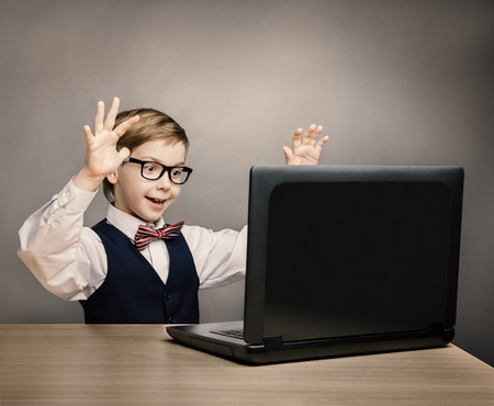 Child With Laptop, Little Boy in Glasses Happy Amazed Looking at Computer, School Kid Raised Hands over Gray Background, Internet Concept Archivio Fotografico