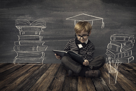 child education: Child Little Boy in Glasses Reading Book over School Black Board with Chalk Drawing, Kids Preschool Development, Children Education Concept