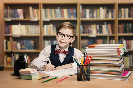 Školní Kid Studium v knihovně, dítě psát na papíře knihy v učebně s policemi