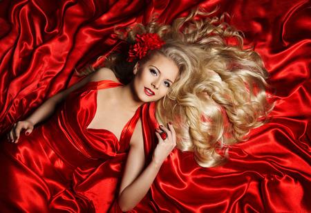 Haar Model, Mode Woman Blonde Liegen auf Red Seidenstoff, Mädchen posiert mit lange lockige Frisur, Haarpflege-Konzept