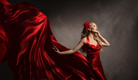 silk cloth: Modello in vestito rosso, Glamour donna che propone in panno di volo lungo di seta su Vento, Bellezza Moda Ritratto Archivio Fotografico