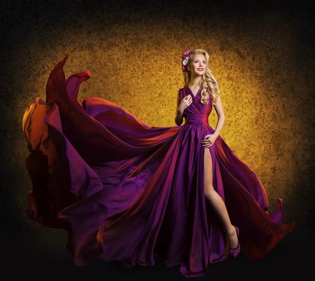 traje de gala: Modelo en vestido p�rpura, la mujer que presenta en Flying pa�o de seda ondeando en el viento, Retrato Moda Belleza