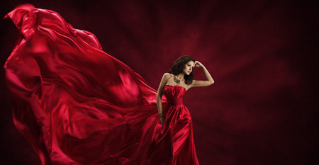 Red Dress, Vrouw in Flying Fashion Silk Fabric Kleding Model Poseren met Blazen Zwaaien Doek, Beauty Concept Stockfoto