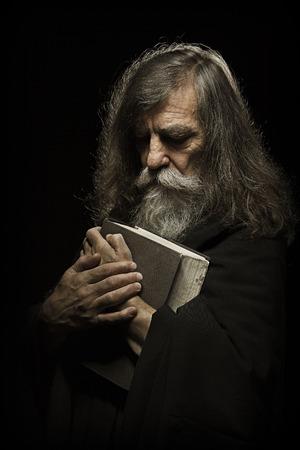 moine: Prière principal Old Man Prier avec les mains sur la Bible livre sur fond noir Banque d'images