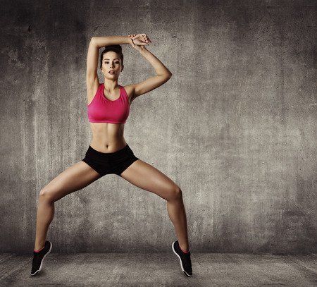 motion: Kvinna Fitness Gymnastik motion, idrott Ung flicka Fit Dans, Modern Aerobic Dancer, Grunge Wall Stockfoto