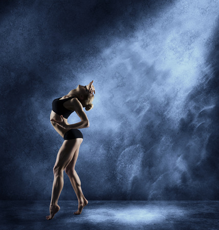 Dancing Woman Sexy Girl Posing in Expressive Sport Dance Fitness Dancer Athletic Body Artist over blue grunge background