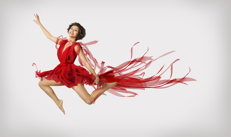 Woman Running in Jump Girl Performer Leap Dancing in Red Dress over light gray background photo