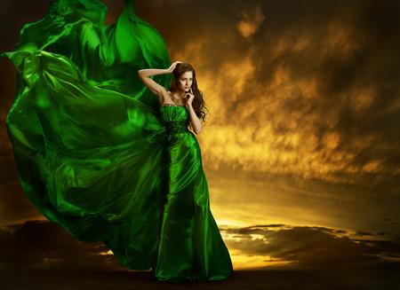 Woman Fashion Dress Fluttering On Wind, Elegant Girl Portrait, Model Posing In Green Silk Gown Fabric, Cloth Waving Over Night Sky Foto de archivo