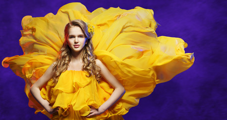Fashion Model Girl in Yellow Dress, Young Woman Posing in Flowing Fabric over Blue Studio Background