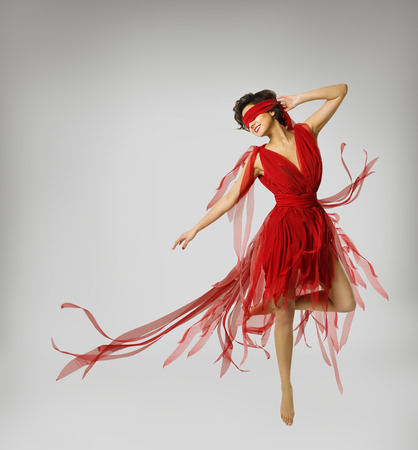 Woman Artist Dancing in Red Dress, Girl with Band on Eyes, Model with Ribbon Bandage over light gray background photo