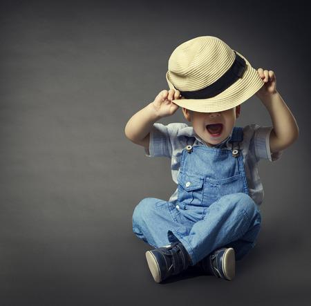 Bebé en pantalones vaqueros de moda, Sombrero ojos cubiertos. Niño Belleza Estilo, Chico bien vestido Sentado sobre fondo gris