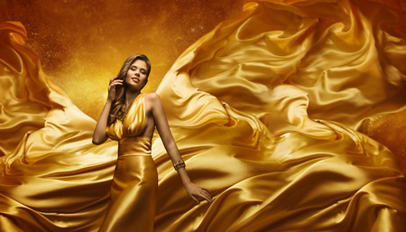 Fashion Model in Gold Dress, Beauty Woman Posing over Flying Waving Cloth, Girl with Yellow Dynamic Silk Fabric Stockfoto