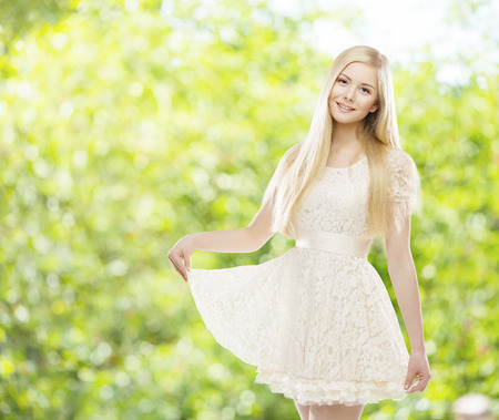 white dresses: Woman White Summer Lace Dress, Young Girl Blond Long Straight Hair, Fashion Model Posing over Green unfocused background