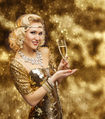 festivity: Rich Woman with Champagne Glass, Retro Lady Celebrating in Shining Gold Dress, VIP Girl in Golden Gown Stock Photo