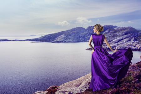 романтика: Женщина в фиолетовый платье, глядя на горы море, размахивая Платья Полет на ветру, элегантный девушка ждет на побережье