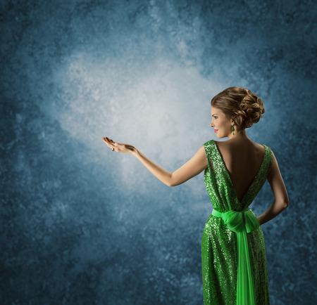 vestidos antiguos: Mujer en vestido verde muestra la mano vacía elegante Modelo en Rich Vestido de exhibición de la joyería sobre fondo azul Vista trasera trasero